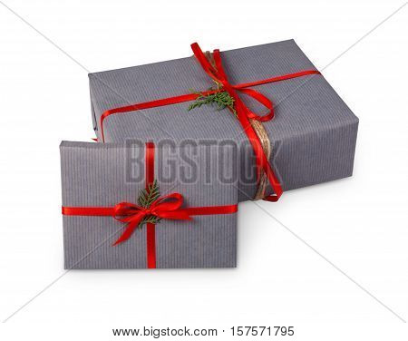 Gift boxes wrapped with gray paper and satin ribbon, decorated with fir tree branches isolated on white background. Modern present for winter holidays