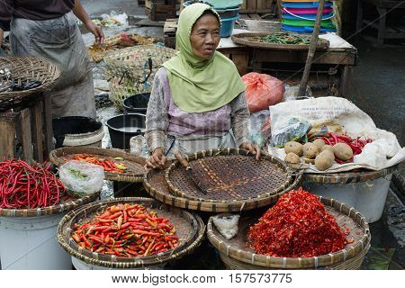 Indonesian woman selling variety of chili peppers at the market in Semarang. January 9 2014 - Java Indonesia