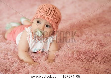 Cute smiling newborn baby six months old dressed fashionable with soother