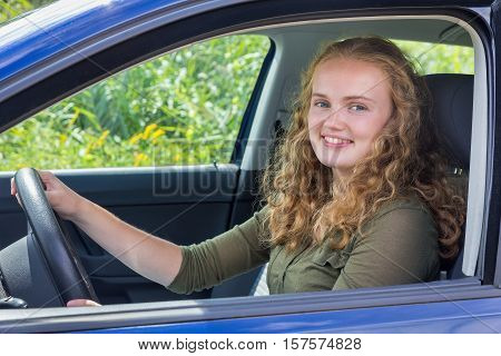 Portrait of young dutch woman holding steering wheel driving car