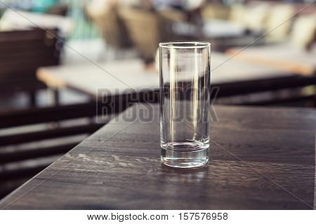 Empty transparent cylindrical glass over wooden table at restaurant outdoor terrace extreme shallow of depth fieldspace for copy text