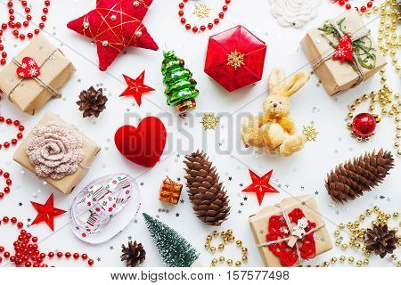 Christmas and New Year background with decorations. Gifts in craft paper pine cones red hearts and confetti. Flay lay top view.