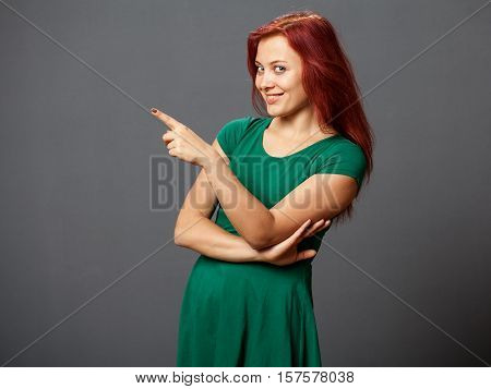 Young naughty woman pointing out by the finger and looking to the camera gray background