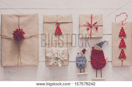 Christmas background. Top view of gift boxes and funny birds toys. Presents in craft paper with red ribbon bows and spruce tree on white wood. Celebration of winter holidays concept