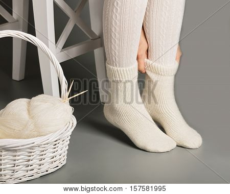 Female feet in white knitted stockings and socks near the basket with yarn and knitting.