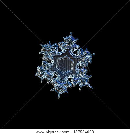 Snowflake isolated on black background. This is closeup image of real snow crystal: medium size stellar dendrite with big and empty central hexagon and complex inner pattern at six arms.