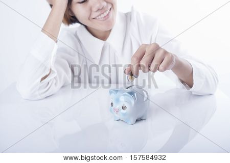 business women hand putting coin money into piggy bank. concept saving finance and investment.