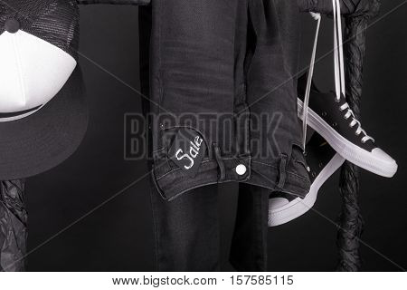 Sale Sign. Black And White Snaekers, Cap  Pant, Jeans Hanging On Clothes Rack   Background.  Friday.