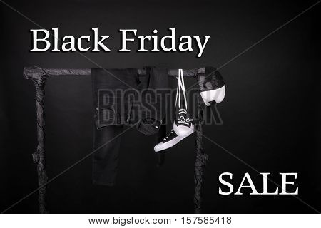 Black Friday. Sale Sign.  And White Sneakers, Cap  Pant, Jeans Hanging On Clothes Rack   Background.