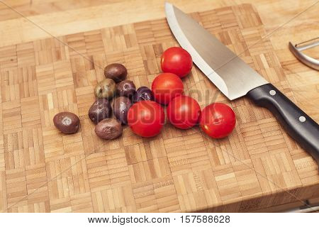 Tomatoes and brown olives on wooden chop board with kitchen knife ready for chopping