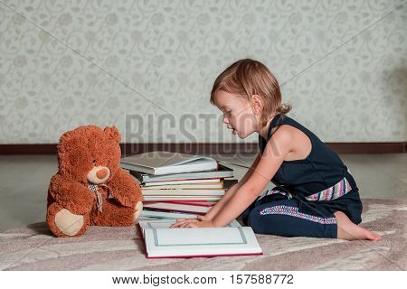Little Girl In  Dark Blue Dress Reading  Book Sitting On The Floor Near Teddy Bear. Child Reads Stor