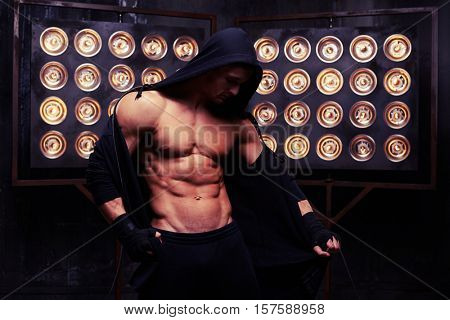 Mid shot of muscular man in studio lights. Bare-chested muscular male taking off a black hoodie while standing over black background