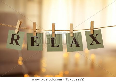 Word RELAX made of cards with printed letters hanging on cord against blurred background
