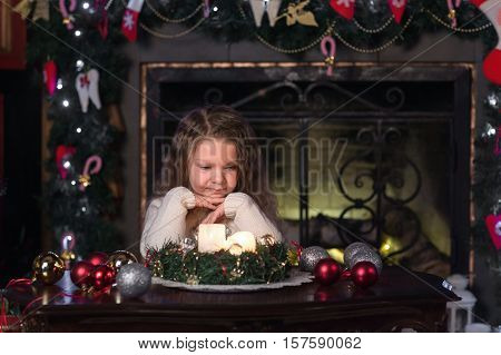 girl makes a wish at Christmas near tree at home