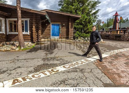 Young man standing on the line of the arctic circle in Rovaniemi Finland.