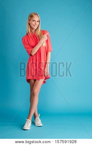 Full length portrait of a smiling happy woman in red dress standing and pointing finger away isolated on the blue background