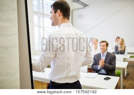 Businessman as a speaker receiving applause from the audience during a business workshop