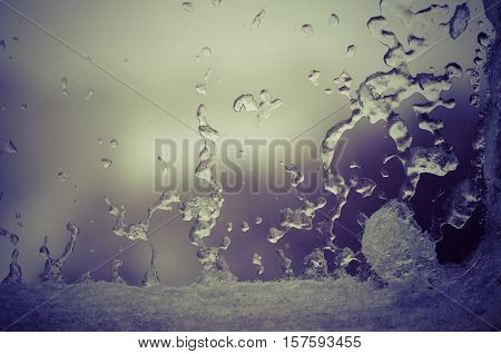 Ice water drops on winter glass. Frost patterns on window in evening. Frosty natural pattern on winter window. Ice on a window background texture. Light frozen window glass background.