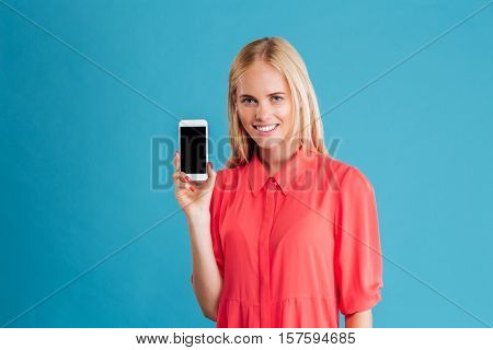 Portrait of a happy casual woman showing blank smartphone screen over blue background