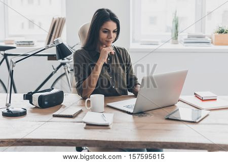 New solution every day. Confident young woman in smart casual wear working on laptop while sitting at her working place in office