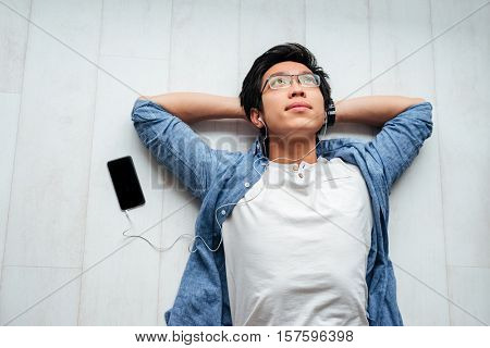 Happy asian man in shirt on the floor. with phone. listening music