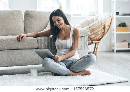 Examining her new tablet. Attractive young woman looking at her digital tablet and smiling while sitting on the carpet at home