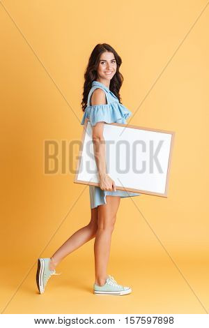 Side view of a cheerful smiling woman holding white blank board isolated on the orange background