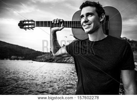 Handsome smiling guitarist. Black-white outdoor photo. Thailand.