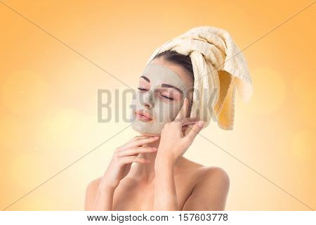 beautiful Young girl takes care her skin with cleansing mask on face and towel on head isolated on white background. Health care concept. Body care concept. Young woman with healthy skin.