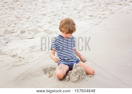 Adorable active little kid boy having fun on Naples beach, Florida. Happy cute child building sand castles.