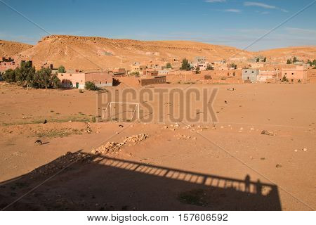 Part of an old medieval city Ait ben Haddou. Houses with few trees and a hill in the background. Shadow of a traditional building.