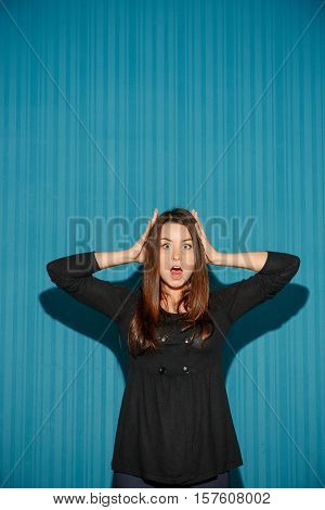 Portrait of young woman with shocked facial expression over blue studio background