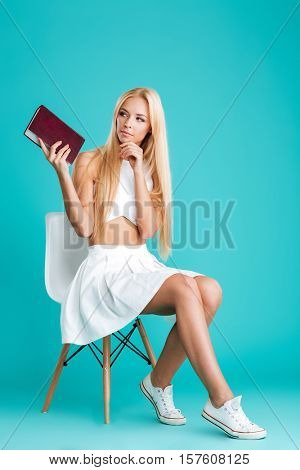 Full length portrait of a pensive young woman holding book whie sitting on chair isolated on the blue background