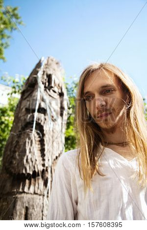 Slavic pagan young long-haired man next to a wooden pole idol sculpture. Traditional Russian culture - religion and art