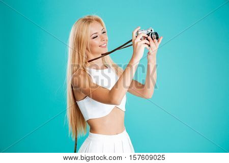 Portrait of a beautiful smiling woman taking picture with retro camera and looking away isolated on the blue background