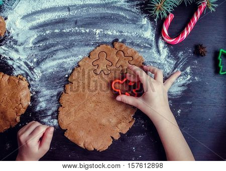 Little girl's hand making traditional Christmas cookies. Raw dough and cutters for the holiday cookies on a dark table. Preparing Christmas gingerbread men. Steps of making biscuits. Top view.