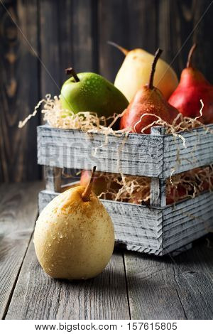 Red green yellow sweet pear and one apple in the old wooden box on a dark background. Selective fokus.Rustik style