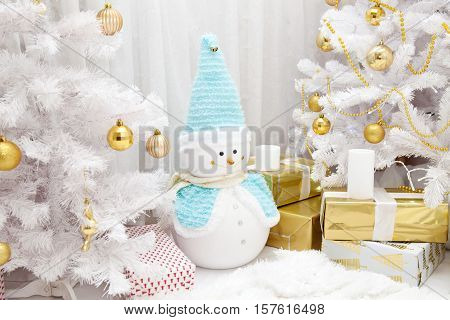 White snow-covered Christmas tree with gold balls and decorative Christmas snowman in the ambience