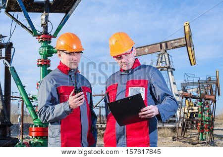 Two workers in the oilfield checking test results. Pump jack and wellhead background. Oil and gas concept.