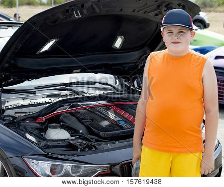the boy at an open cowl of the sports car a subject automotive equipment and children