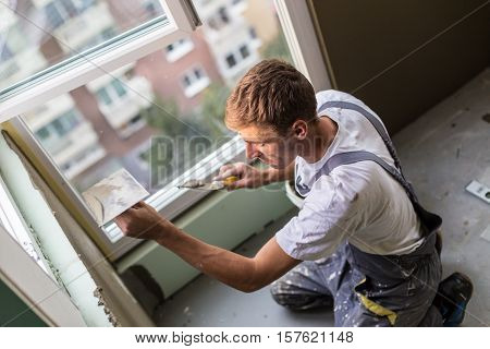 Thirty years old manual worker with wall plastering tools renovating house. Plasterer renovating indoor walls and ceilings with float and plaster. poster