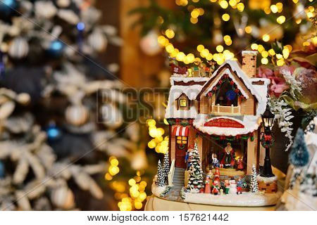 Adorable christmas music toy house with miniature santa presents decorated tree bokeh background. Celebration holidays