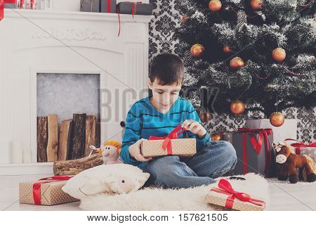Cute happy boy unwrap christmas present box on holiday morning in beautiful room interior. Male child open Xmas gifts near big decorated fir tree and fireplace. Winter holidays concept