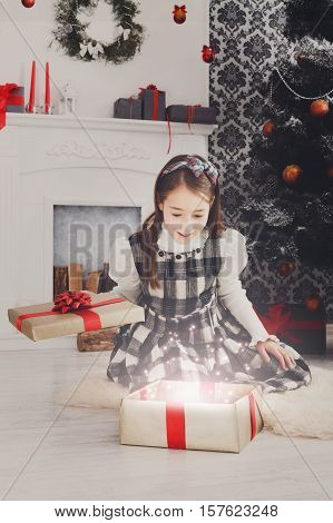 Christmas miracle. Beautiful happy excited girl unwrap magic present on holiday morning in beautiful room. Female child open Xmas gift near decorated fir tree and fireplace. Winter holidays concept