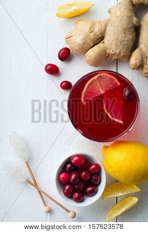 Fresh cranberry juice with lemon berry ginger and sugar on a light background. Top view. Space for text. Selective focus.