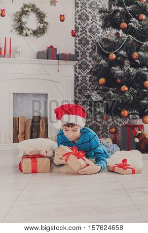 Cute happy boy in santa hat unwraps christmas present box on holiday morning in beautiful room interior near big decorated fir tree and fireplace. Winter holidays concept