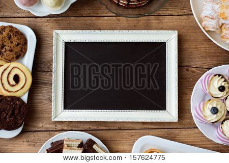 Table with picture frame, cake, cupcakes, cookies and cakepops. Studio shot on brown wooden background. Copy space. Flat lay.