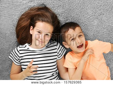 Brother and sister lying on carpet