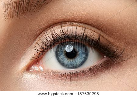 Close up view of beautiful blue female eye. Good vision contact lenses trust or observation concept