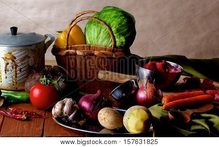 Arrangement of Raw Ingredients with Vegetables Meat Spices and Kitchen Dish Ware closeup on Wooden background. Dutch Still Life Styled